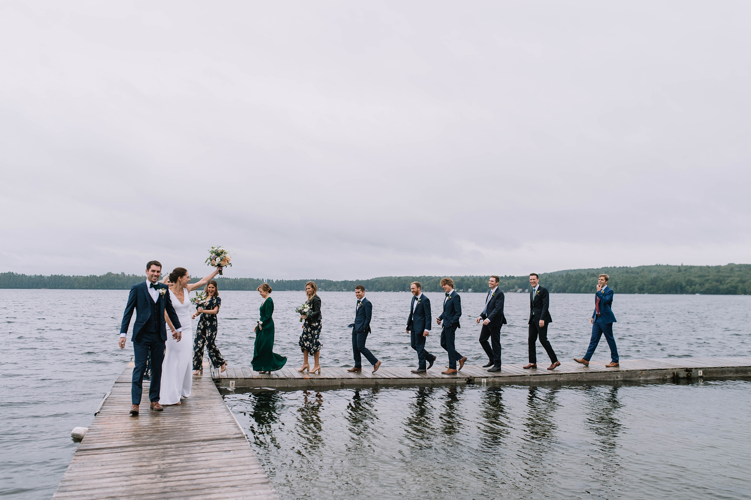 Wedding party celebrating on lakeside docks